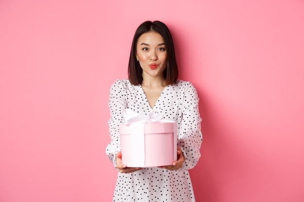 Linda namorada asiática parabenizar com o dia dos namorados, dando um lindo presente romântico na caixa, lábios franzidos para beijo, em pé sobre um fundo rosa