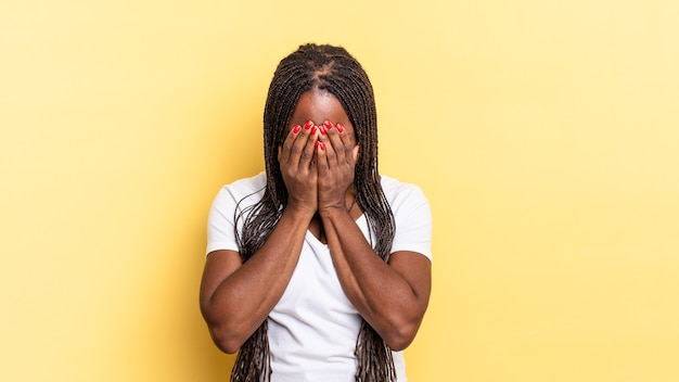 Linda negra negra se sentindo triste, frustrada, nervosa e deprimida, cobrindo o rosto com as duas mãos, chorando