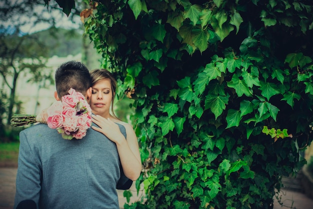 Linda noiva abraçando o noivo e segurando o buquê no dia do casamento em um parque natural