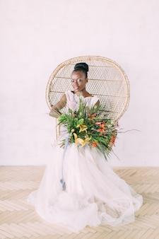 Linda noiva afro-americana com buquê tropical em estúdio, sentado na cadeira