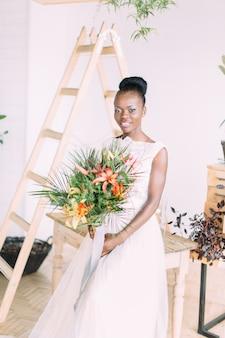Linda noiva afro-americana com buquê tropical em estúdio