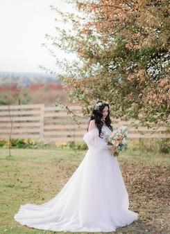 Linda noiva caucasiana com buquê de casamento está de pé na grama seca perto de árvore no dia quente de outono