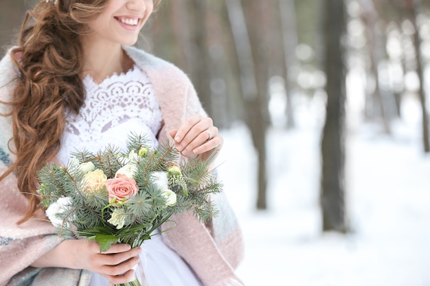 Linda noiva com buquê ao ar livre no dia de inverno, closeup