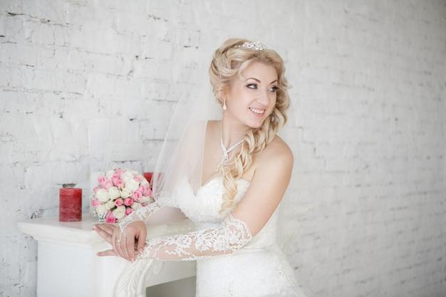 Linda noiva com buquê de casamento em pé perto da lareira