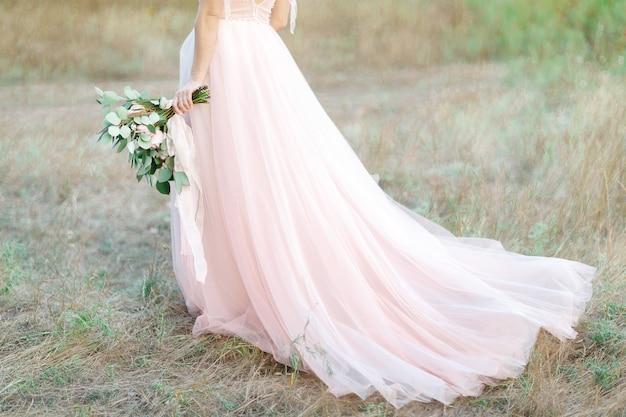 Linda noiva com buquê e vestido com cauda na natureza. fotografia de belas artes.