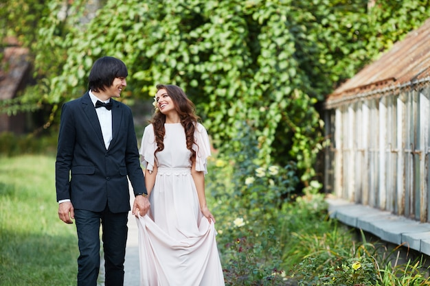 Linda noiva com cabelo longo cacheado e noivo em pé perto um do outro no fundo de folhas verdes, foto de casamento, lindo casal, dia do casamento, retrato.
