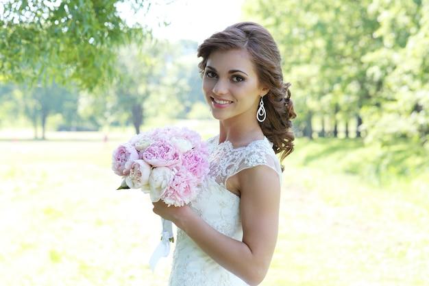 Linda noiva com penteado encaracolado na natureza