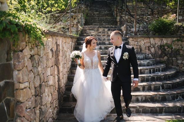 Linda noiva com seu noivo bonito andando lá fora no dia do casamento.