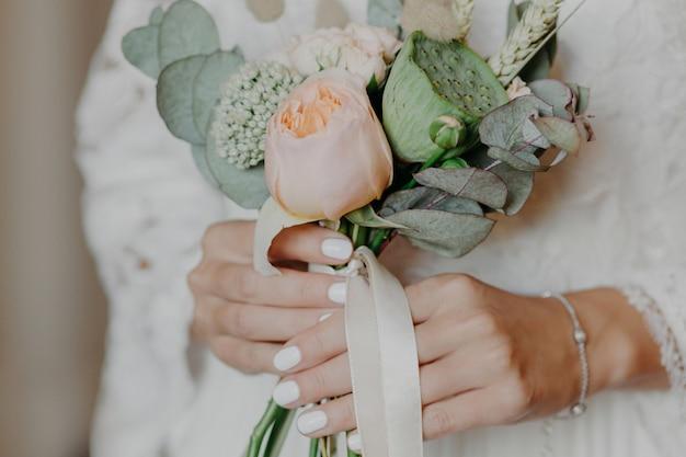 Linda noiva com um belo buquê se prepara para a cerimônia de casamento. mãos de noivas segurar flores indoor.