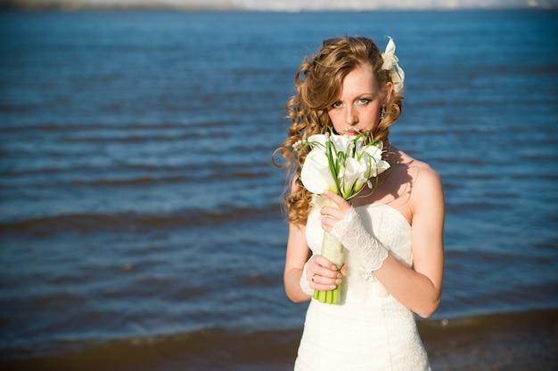 Linda noiva com um buquê de lírios na costa do rio no verão