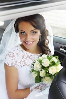 Linda noiva com um buquê de rosas sentada no carro