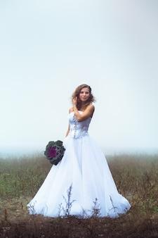 Linda noiva com um buquê em um campo nebuloso
