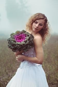 Linda noiva com um buquê em um fundo de um campo nebuloso