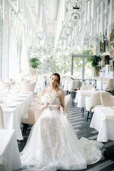 Linda noiva com um buquê na mão sentada em um restaurante no dia do casamento