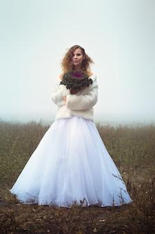 Linda noiva com um buquê no fundo de um campo nebuloso