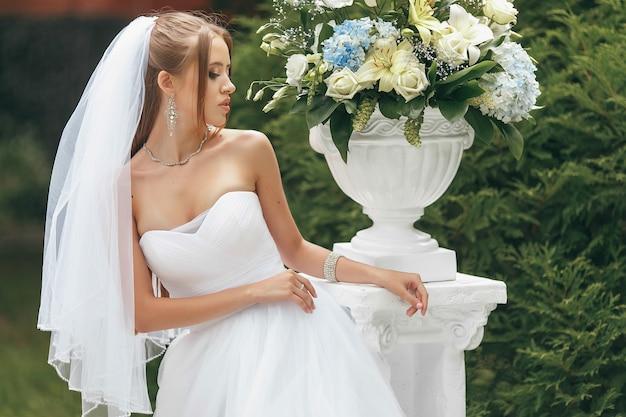 Linda noiva com um magnífico vestido de noiva posando no meio da vegetação