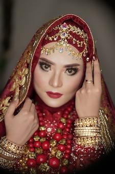 Linda noiva com um vestido vermelho e dourado