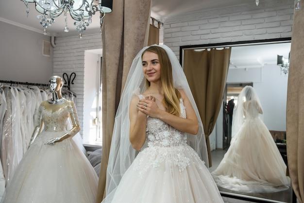 Linda noiva com vestido de noiva em pé na boutique