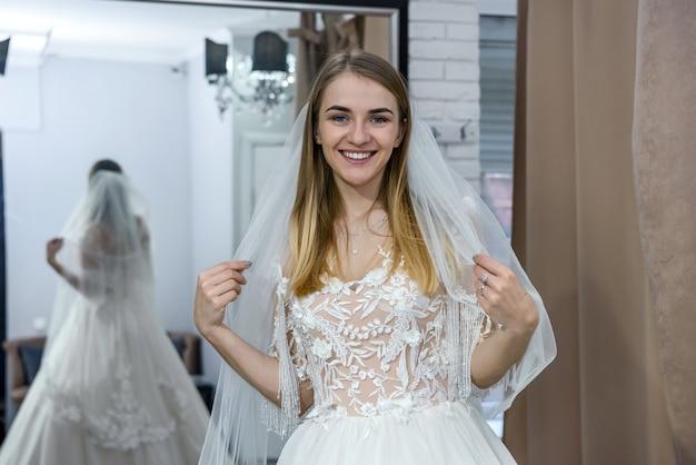Linda noiva com vestido de noiva posando em frente ao espelho