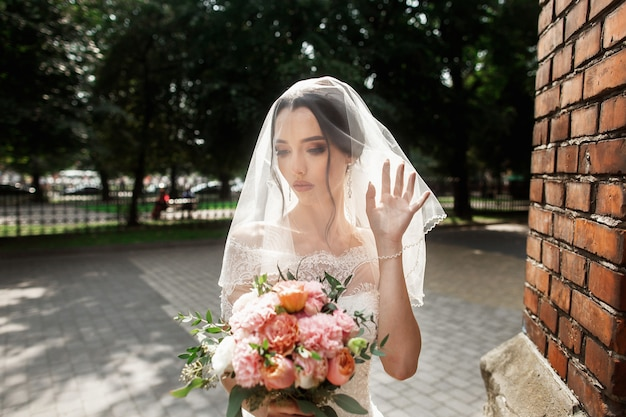 Linda noiva com véu de noiva no rosto posando perto da parede vermelha da antiga igreja gótica
