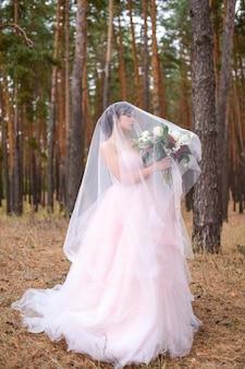 Linda noiva de vestido rosa fica escondido sob o véu em uma floresta