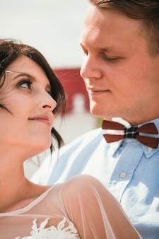 Linda noiva e noivo se abraçando e se beijando no dia do casamento ao ar livre
