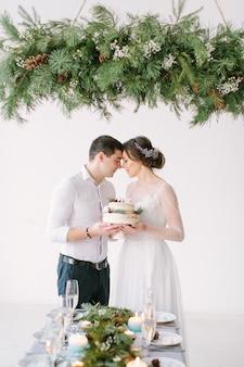 Linda noiva e o noivo se olham à mesa na sala de banquetes e segurando o bolo de casamento decorado com frutas e algodão