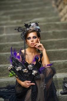 Linda noiva elegante em um vestido preto senta-se na escada em florença, itália.