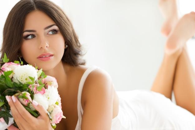 Linda noiva em lingerie branca segurando buquê nupcial