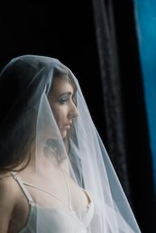 Linda noiva em lingerie branca, sentada no quarto e no estúdio. manhã do conceito de casamento