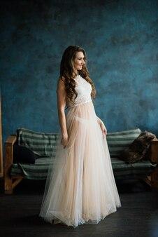 Linda noiva em lingerie branca, sentada no quarto e no estúdio.