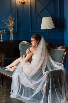 Linda noiva em lingerie de renda branca, com ombro nu, sentada em um quarto de hotel, boudoir. feliz manhã de casamento.