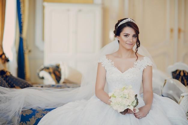 Linda noiva em um magnífico vestido branco e uma coroa na cabeça