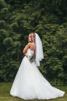 Linda noiva em um magnífico vestido de noiva posando no meio da vegetação na rua.