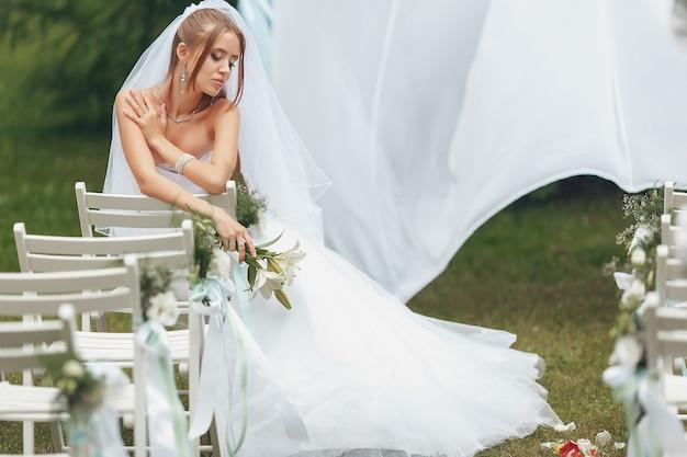 Linda noiva em um magnífico vestido de noiva posando no meio da vegetação na rua