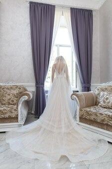 Linda noiva em um vestido chique em vista traseira do quarto elegante. mulher em vestido de renda longa com laço e véu com grande janela e poltrona. manhã da noiva no interior elegante. dia do casamento