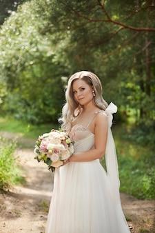 Linda noiva em um vestido de noiva luxuoso com um buquê de noiva com flores de peônia e rosas