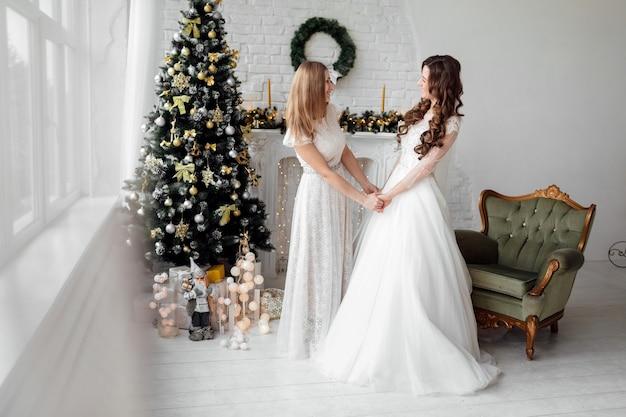 Linda noiva em vestido de noiva de luxo e linda dama de honra em vestido de natal decorado. weddind no natal.