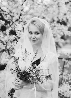 Linda noiva em vestido de noiva e bouquet de noiva, mulher feliz recém-casada com flores do casamento, mulher com penteado e maquiagem de casamento.