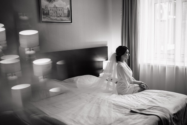 Linda noiva feliz senta-se em uma cama. noiva com maquiagem e penteado elegante. dia do casamento. beleza, moda noiva com véu longo. feliz dia das noivas.