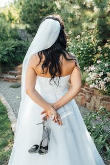 Linda noiva fica de costas e segura seus sapatos e uma taça de champanhe.