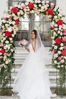 Linda noiva fica sob o altar de casamento feito de flores vermelhas e brancas