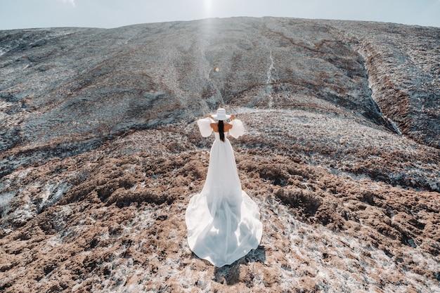 Linda noiva irreconhecível em um vestido de noiva e um chapéu no topo das montanhas de sal. linda jovem noiva com um chapéu. dia do casamento. belo retrato da noiva sem o noivo.
