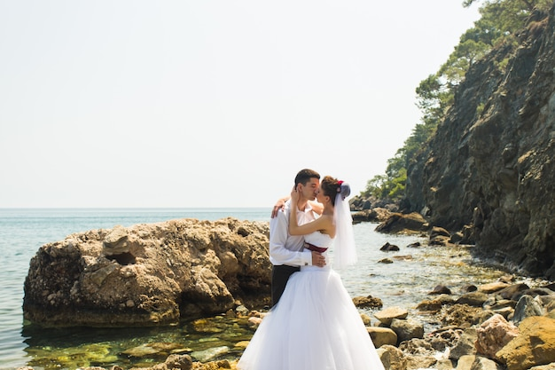 Linda noiva linda e noivo elegante na praia