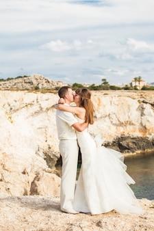 Linda noiva linda e noivo elegante nas rochas.