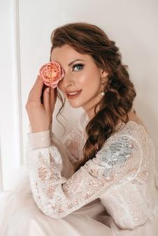 Linda noiva loira com buquê de flores da primavera ao ar livre.