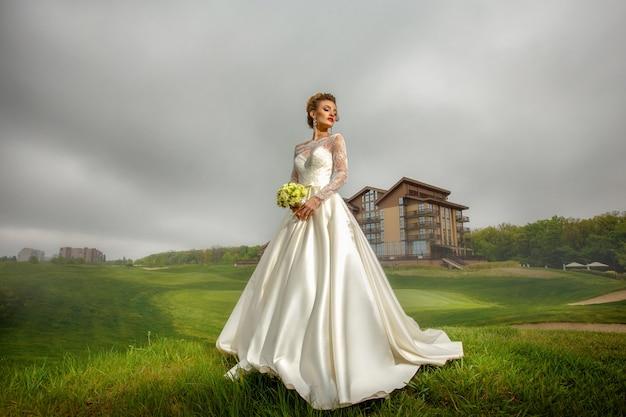 Linda noiva loira em terno de casamento e buquê nas mãos ao ar livre