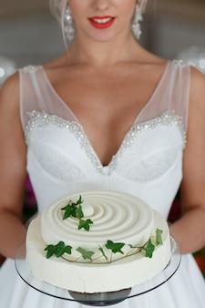 Linda noiva loira segurando um bolo de casamento. o foco fora do bolo.