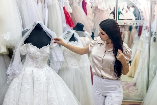 Linda noiva morena escolhendo vestido para casamento