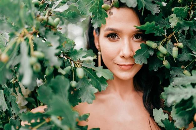 Linda noiva olhando através de folhas de árvore.